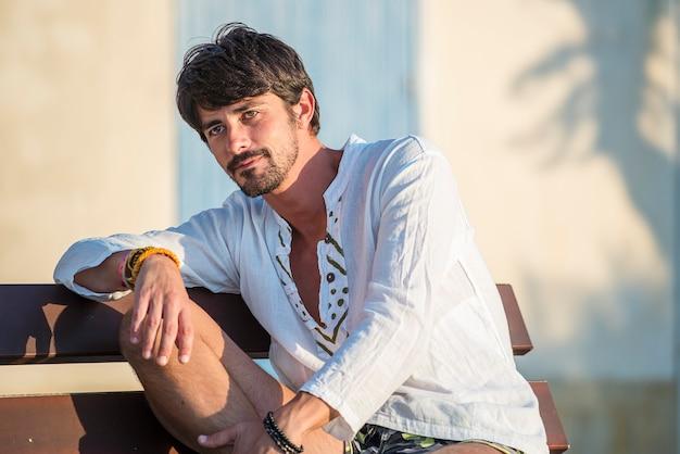 Beau jeune homme assis à l'extérieur en journée d'été dans un village méditerranéen au coucher du soleil
