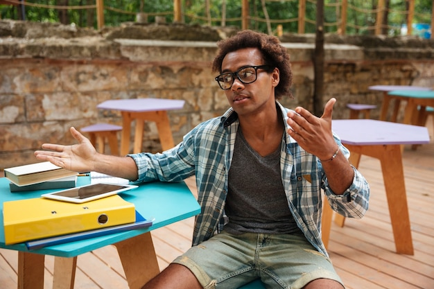 Beau jeune homme assis et parlant dans un café en plein air