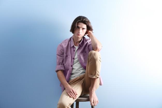 Beau jeune homme assis sur un tabouret sur fond bleu