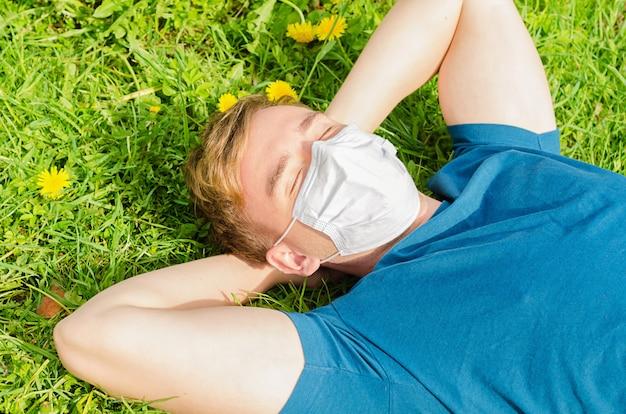 Beau jeune homme au visage masque médical se trouve sur l'herbe verte