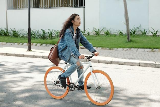 Beau jeune homme aux cheveux longs à vélo se dépêchant d'aller à l'université ou au travail