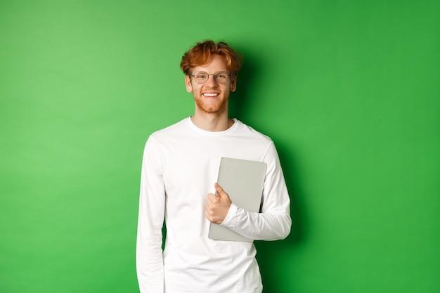 Beau jeune homme aux cheveux rouges, portant des lunettes et un t-shirt à manches longues, tenant un ordinateur portable sur fond vert.