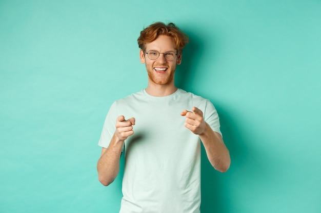 Beau jeune homme aux cheveux roux, portant des lunettes et un t-shirt, pointant le doigt vers la caméra et souriant, vous choisissant, vous félicitant ou louant, debout sur fond menthe