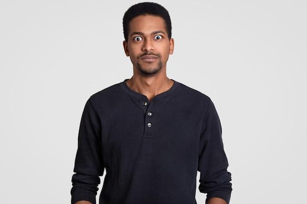 Beau jeune homme aux yeux écarquillés, a une petite barbe, habillé nonchalamment, étonné par les dernières nouvelles, regarde un film d'horreur, isolé sur blanc. concept de réaction
