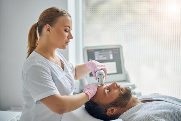Beau jeune homme aux yeux fermés allongé sur un lit de repos tout en recevant un traitement facial au laser dans une clinique cosmétologique