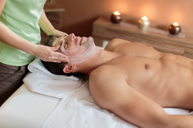 Beau jeune homme ayant un massage du visage