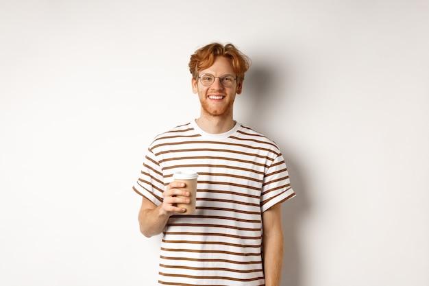 Beau jeune homme avec barbe et cheveux rouges en désordre, portant des lunettes avec t-shirt rayé, buvant du café à emporter et souriant, fond blanc.