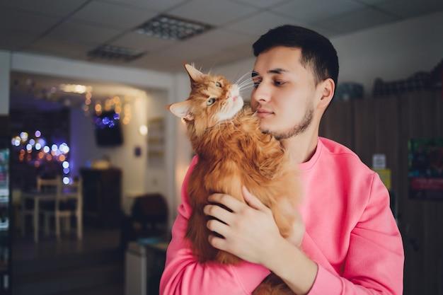 Beau jeune homme avec une barbe étreignant le chat maine coon à tête rouge. mec en t-shirt blanc tenant des chatons en mains amoureux des animaux.