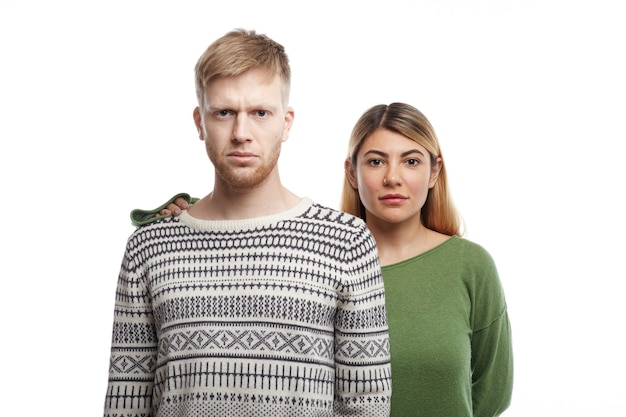 Beau jeune homme avec barbe regardant avec un regard sérieux exprimant la disponibilité et la confiance, sa petite amie de soutien debout derrière lui avec sa main sur son épaule