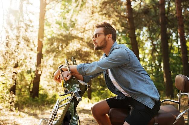 Beau jeune homme barbu assis sur un scooter à l'extérieur