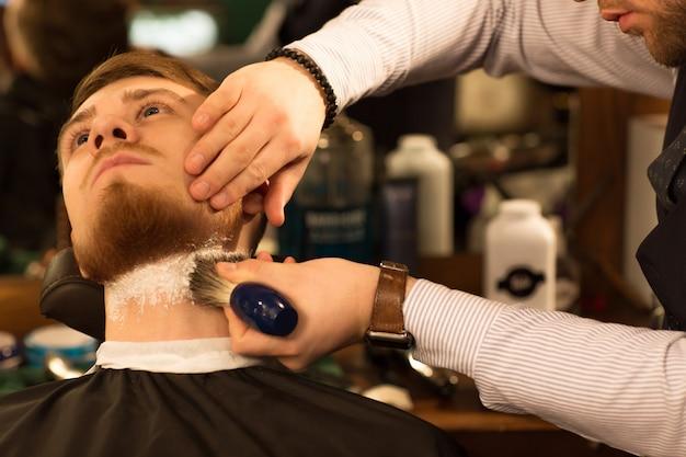Beau jeune homme barbu au salon de coiffure