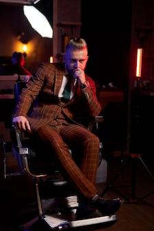 Beau jeune homme barbu dans un smoking assis dans une pièce sombre dans des vêtements à la mode pour la soirée festive