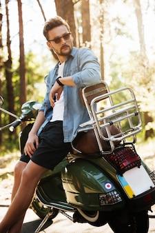 Beau jeune homme barbu debout près de scooter à l'extérieur