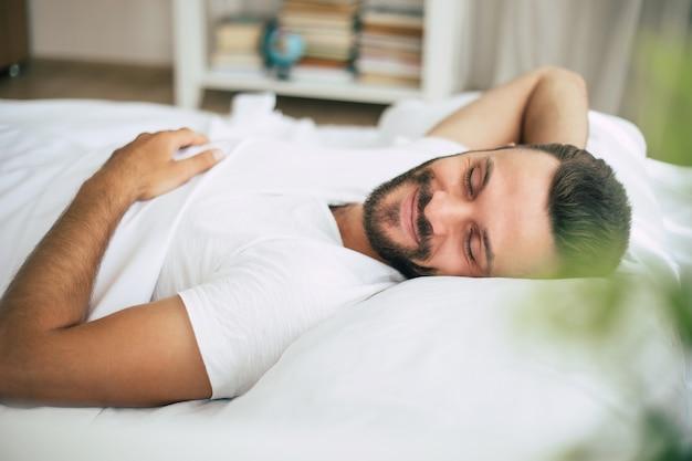 Beau jeune homme barbu dort dans un grand lit blanc dans une chambre confortable
