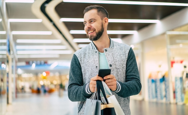 Beau jeune homme barbu élégant souriant avec des sacs à provisions utilise un téléphone intelligent tout en marchant dans le centre commercial
