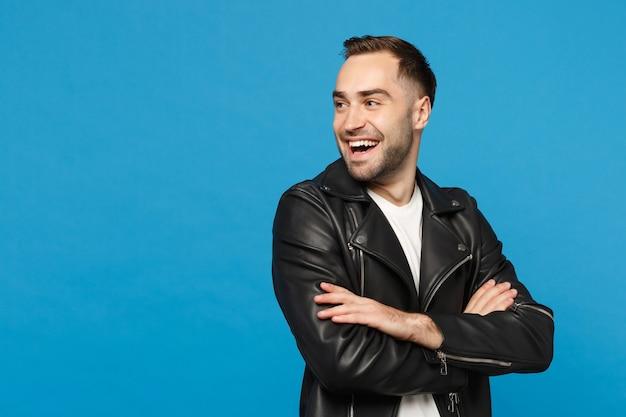 Beau jeune homme barbu élégant en t-shirt blanc avec veste en cuir noir regardant de côté isolé sur fond de mur bleu portrait en studio. concept de mode de vie des émotions sincères des gens. maquette de l'espace de copie.