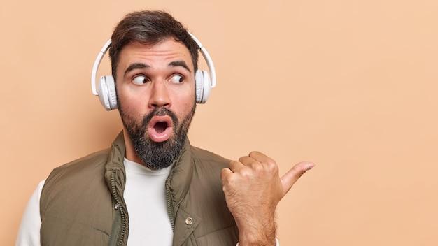 Beau jeune homme barbu garde la bouche ouverte pointe le pouce loin