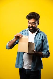 Beau jeune homme barbu indien ouvrant la boîte avec colis en se tenant debout sur le jaune