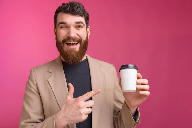 Beau jeune homme barbu pointe sur une tasse de café blanc pour aller sur le mur rose