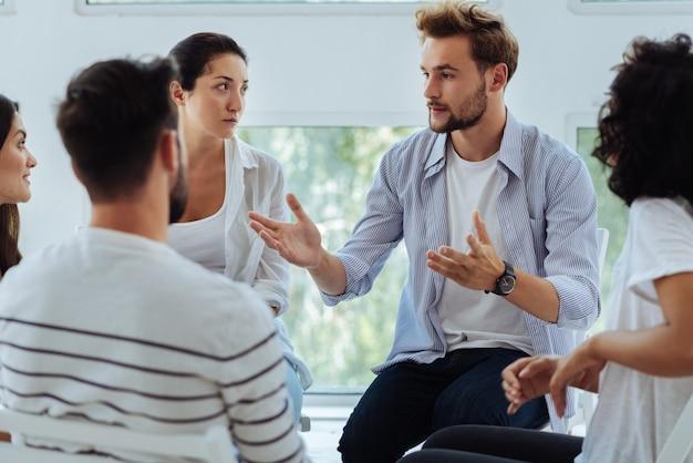 Beau jeune homme barbu racontant son histoire et partageant son expérience personnelle tout en participant à une séance de thérapie de groupe