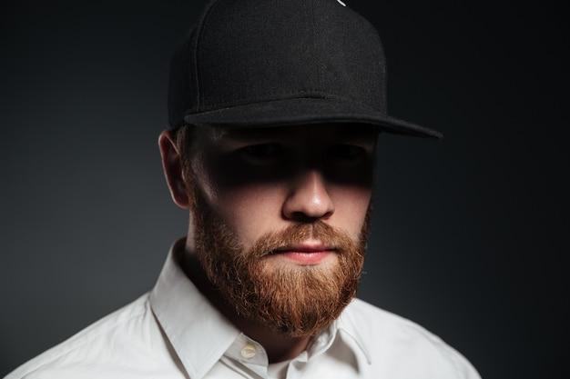 Beau jeune homme barbu sérieux portant une casquette