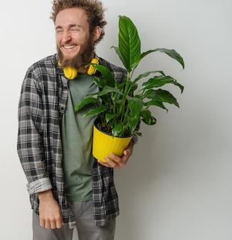 Beau jeune homme barbu souriant tenant un pot de fleur jaune avec une plante habillée en chemise à carreaux et un casque jaune sur son cou isolé sur un mur blanc
