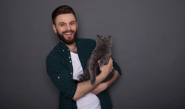 Beau jeune homme barbu souriant tient son joli chat moelleux sur les mains et ils posent ensemble comme les meilleurs amis
