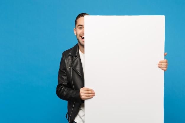 Beau jeune homme barbu tient un grand panneau d'affichage vide blanc pour le contenu promotionnel isolé sur un portrait de studio de fond de mur bleu. concept de mode de vie des émotions sincères des gens. maquette de l'espace de copie.