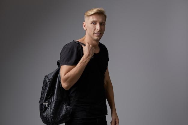 Beau jeune homme blond posant au studio