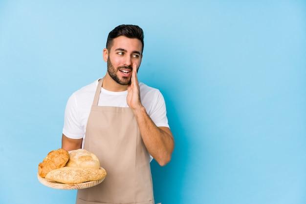Beau jeune homme boulanger isolé dit une nouvelle secrète sur le freinage à chaud et regarde de côté