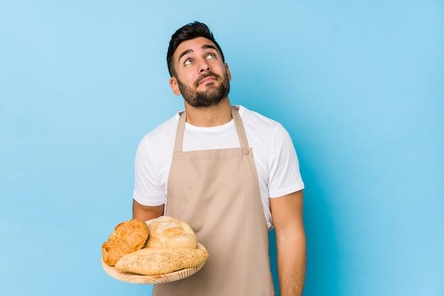 Beau jeune homme boulanger isolé rêvant d'atteindre les buts et objectifs