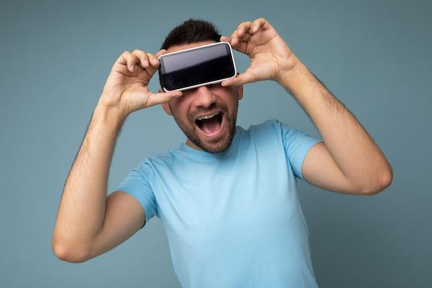 Beau jeune homme brun mal rasé positif avec une barbe portant un t-shirt bleu de tous les jours isolé sur fond bleu tenant et montrant un téléphone portable avec un écran vide pour la maquette.