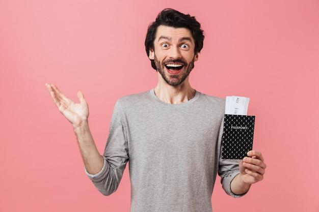 Beau jeune homme brune barbu portant un chandail debout sur rose, montrant le passeport avec des billets d'avion