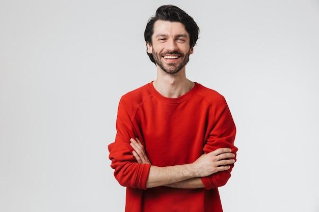 Beau jeune homme brune barbu portant un pull debout isolé sur un mur blanc, les bras croisés