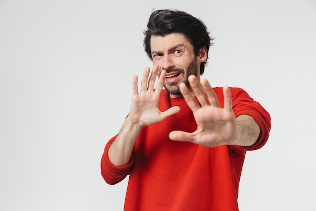 Beau jeune homme brune barbu portant un pull debout isolé sur un mur blanc, mains tendues, arrêt