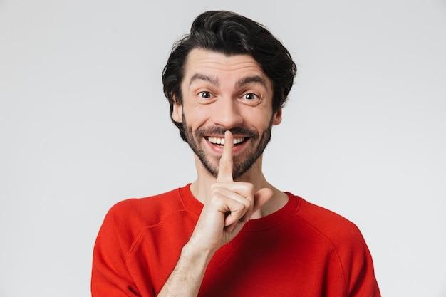 Beau jeune homme brune barbu portant un pull debout isolé sur un mur blanc, montrant un geste de silence