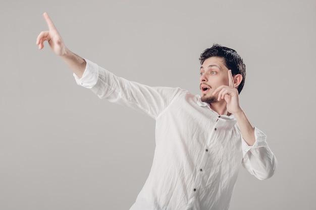 Beau jeune homme brune en chemise blanche dansant et s'amusant sur fond gris. lumière douce
