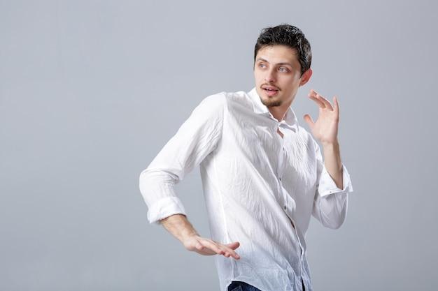 Beau jeune homme brune en chemise blanche dansant et s'amusant sur fond gris.