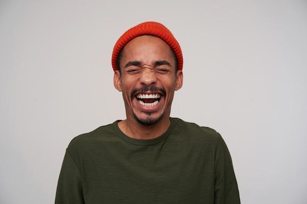 Beau jeune homme brune à la peau sombre joyeuse gardant les yeux fermés tout en riant joyeusement avec la bouche grande ouverte, debout sur blanc