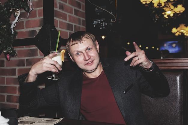 Beau jeune homme buvant un cocktail au bar de nuit à table, regardant la caméra et souriant. concept de mode de vie de la ville de nuit de la vie nocturne. espace de copie