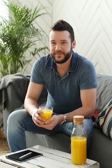 Beau jeune homme buvant du jus d'orange à la maison