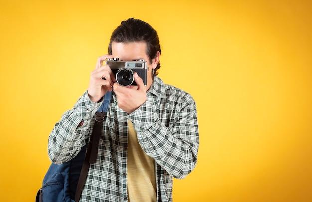 Beau jeune homme, caucasien, avec un appareil photo et un sac à dos, nomade numérique,.