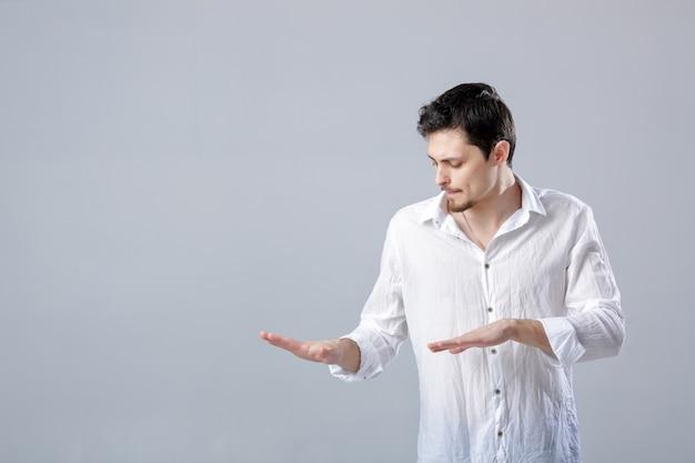 Beau jeune homme en chemise blanche dansant et s'amusant sur gre