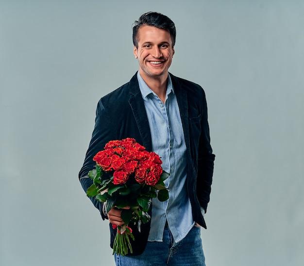Beau jeune homme en chemise bleue et veste est debout avec des roses rouges sur fond gris.