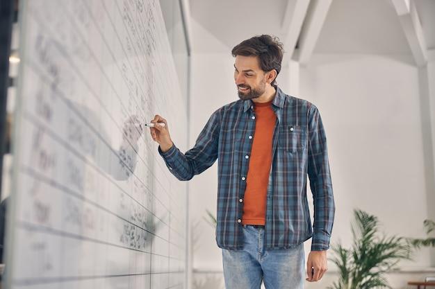 Beau jeune homme en chemise à carreaux écrit à bord du planificateur graphique et souriant