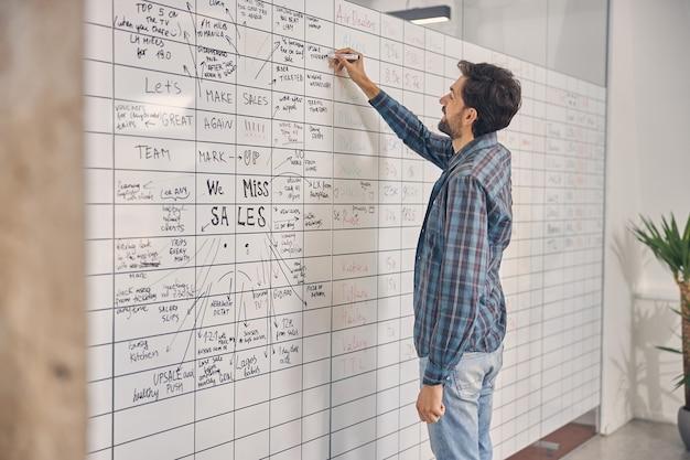 Beau jeune homme en chemise à carreaux remplissant le tableau de planification au travail