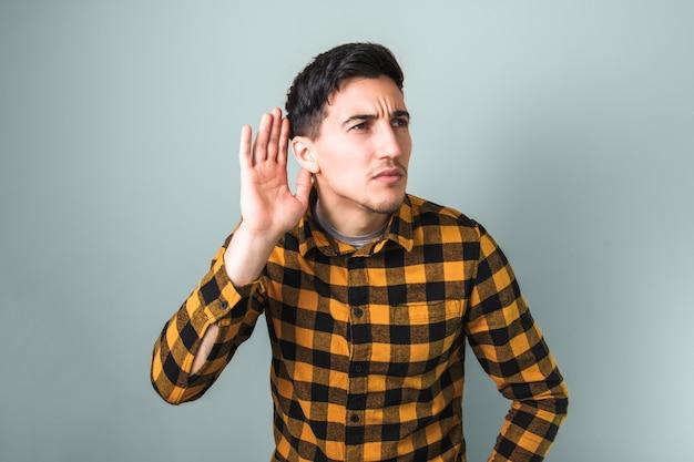 Beau jeune homme en chemise jaune tendance essayant d'entendre quelque chose sur fond gris isolé
