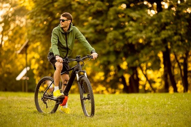 Beau jeune homme chevauchant un vélo électrique dans le parc