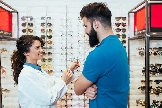 Beau jeune homme choisissant une monture de lunettes dans un magasin d'optique.