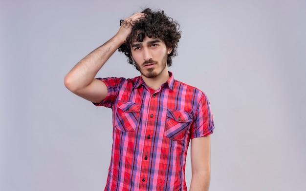 Un beau jeune homme confus aux cheveux bouclés en chemise à carreaux tenant la main sur les cheveux